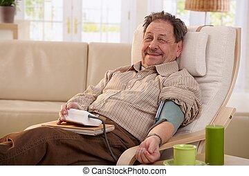 Elderly man measuring blood pressure