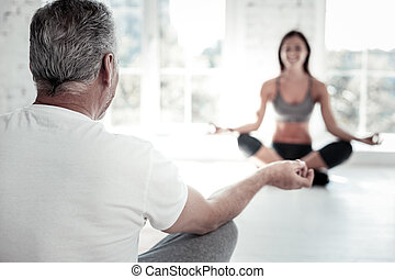 Elderly man meditating during yoga session