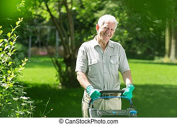 Smiling elderly man mowing the lawn in his garden
