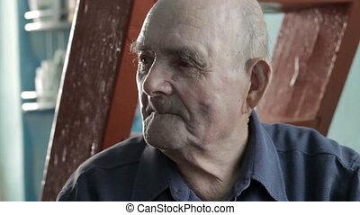 Elderly man observing a room - Elderly man sitting observing...