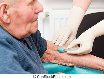 Doctor taking blood sample from elderly patient to monitor anticoagulant treatment.