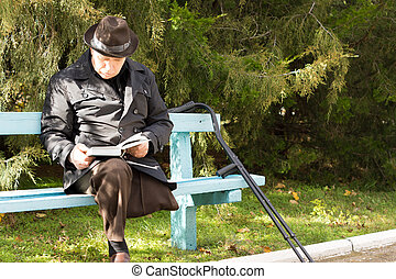 Elderly man on crutches sitting in the sun reading
