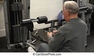 Elderly man does strength training on a row machine.