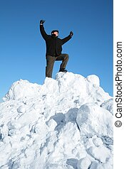 elderly man on top of snow hill with hand up