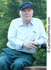 Elderly man enjoying his rest outdoors, while sitting on a picnic bench.