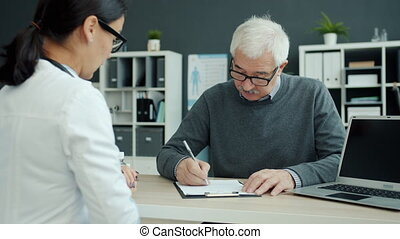 Elderly man patient is signing medical papers during consultation with doctor in hospital sitting at table writing and talking. Medicine and people concept.