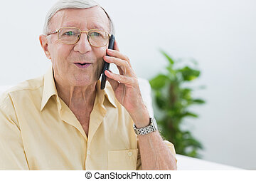 Elderly man phoning in the living room