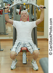 Elderly man playing sports in a gym