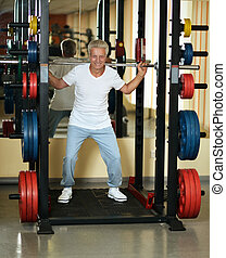 man playing sports - Elderly man playing sports in a gym