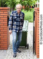 Elderly man pulling a wheeled dumpster, vertical