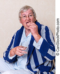 Elderly man putting dentures in