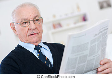 elderly man reading at a newspaper