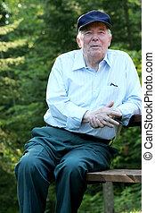 Elderly man relaxing - Elderly man sitting outdoors enjoying...