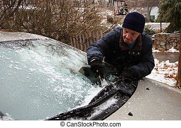 elderly man scraping windshield