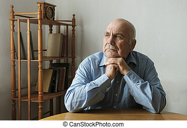 Elderly man seated at a table thinking