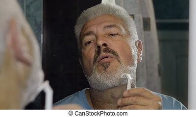 Elderly man shaving and performing various grooming...