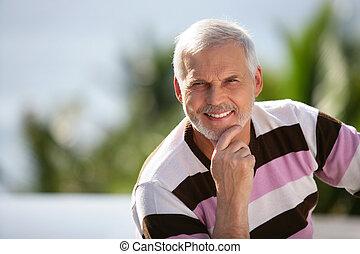 Elderly man sitting in garden