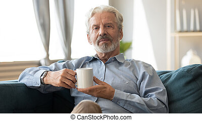 Elderly man sitting on couch holding cup looking at camera...