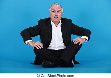 Elderly man sitting on the floor
