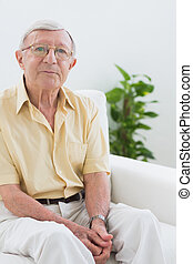 Elderly man sitting on the sofa in the living room