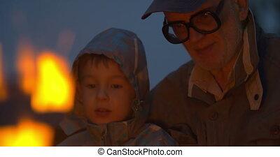 Elderly man sitting with small boy near campfire