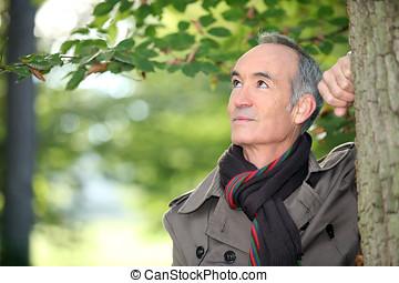 Elderly man strolling in the forest