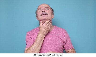 Elderly hispanic man suffering from throat problems