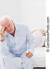 Elderly man suffering while woman sleeping on the bed