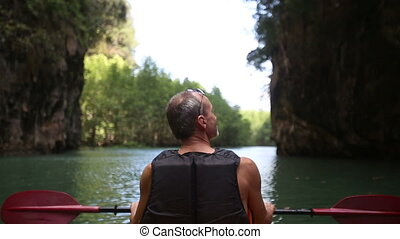 man swim down the river on kayak