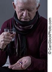 Elderly man taking medicine