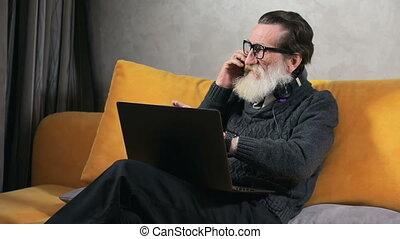Elderly Man Talks on Phone before Laptop