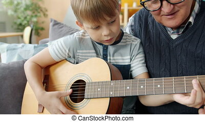 Elderly man grandfather is teaching grandson to play the guitar in apartment bonding enjoying home education. Musical instruments and childhood concept.