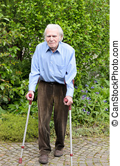 Elderly man using forearm crutches to walk