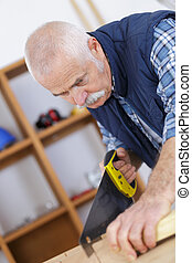 Elderly man using handsaw