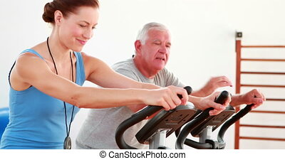 Elderly man using the exercise bike with his trainer at the...