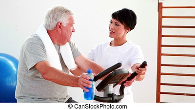 Elderly man using the exercise bike talking to ...