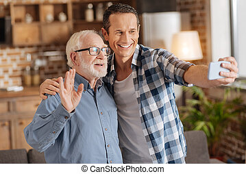 Elderly man waving at camera while taking selifes with son