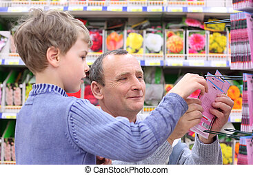 elderly man with boy in shop of seeds