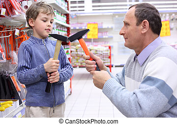 elderly man with boy in shop with hammers in hands