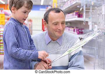 elderly man with boy in store with grill for roasting in hands