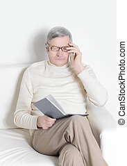 elderly man with digital tablet sitting in a chair.