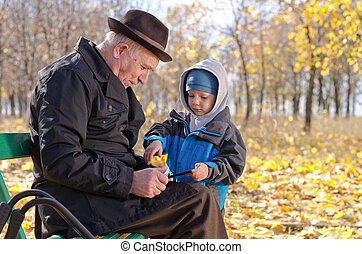 Elderly man with his grandson in the park