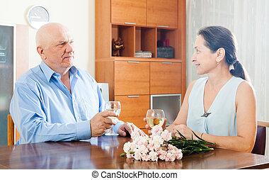 elderly man with mature woman having wine