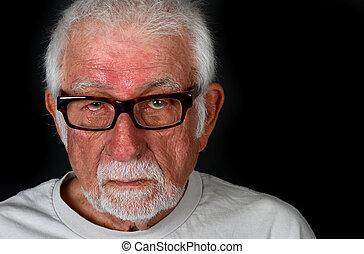 Elderly man with sad expression shedding a tear