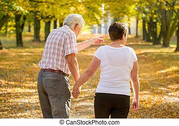 Elderly marriage strolling in park