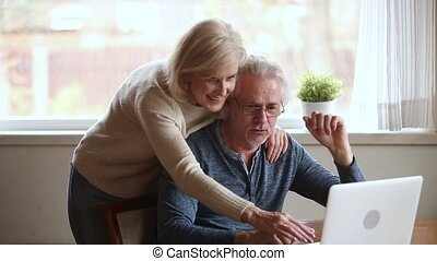 Elderly married couple internet users surfing web site at...