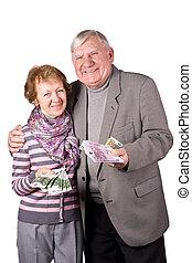 Elderly married couple with money in hands
