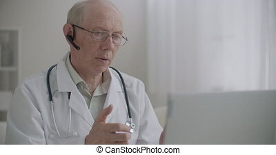 elderly medical specialist is communicating by web camera on laptop from his office in clinic, remotely communication with patients