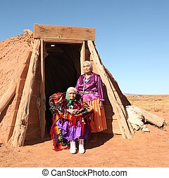 Elderly Native American women pose outside a tribal abode. They are full length viewable and looking at the camera. Squarely framed shot.