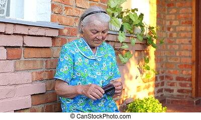 Elderly older female counts money in her wallet